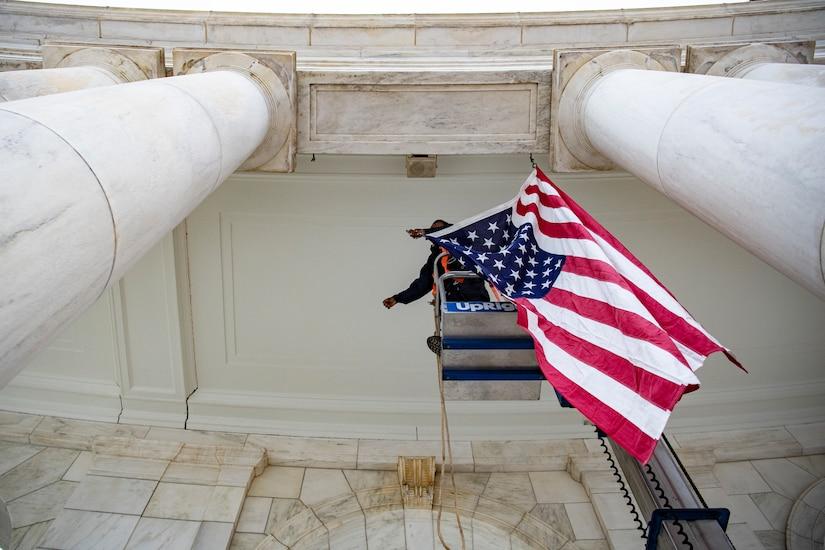 A staff member hangs a flag.
