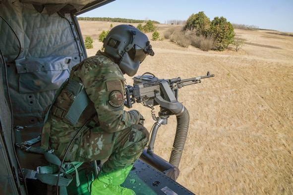 an Airman mans a gun inside of a flying helicopter