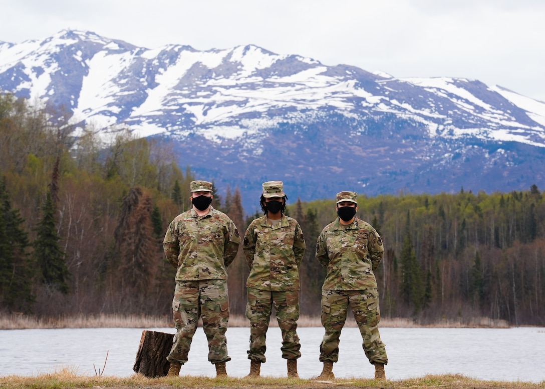 From left to right: Tech. Sgt. Johnathan Thompson, Senior Airman Deniea Turner, and Staff Sgt. Michelle Aguilar-Villafuerte, all members of the 247th Intelligence Squadron, Tennessee Air National Guard, pose with the Chugach Mountains in the background May 12, 2021 at Joint Base Elmendorf-Richardson, Alaska. All three Airmen were in Alaska to support active-duty operations, and to learn new skillsets to bring back to their home unit. (U.S. Air Force photo by Senior Airman Justin Wynn)