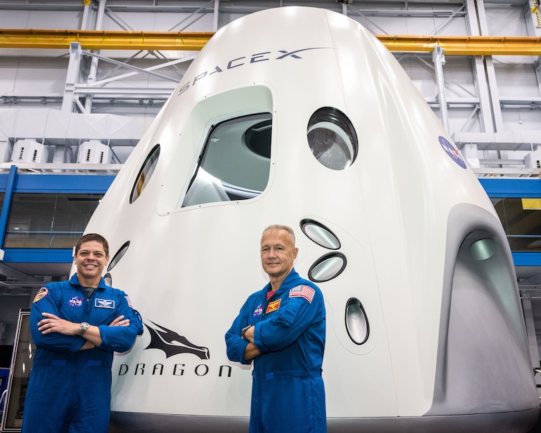 NASA astronauts Bob Behnken and Doug Hurley, assigned to fly on the first test flight of SpaceX's Crew Dragon, pose in front of a mockup of the spacecraft at NASA's Johnson Space Center in Houston, Texas on Aug. 2, 2018 ahead of the agency's announcement of their commercial crew assignment Aug. 3.  Nine U.S. astronauts were selected for commercial crew flight assignments on the first test flights and operational missions for Boeing's CST-100 Starliner and SpaceX's Crew Dragon. Photo Credit: (NASA/Robert Markowitz)