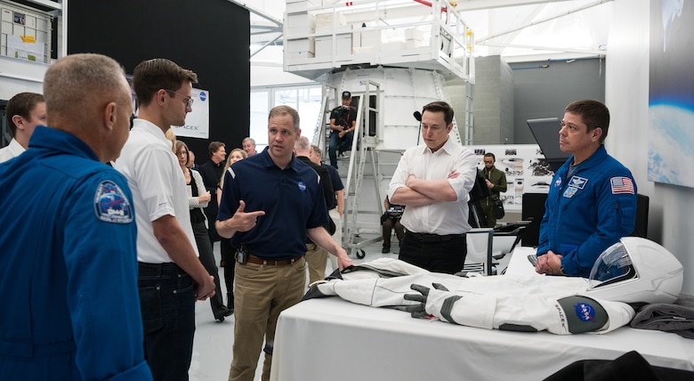 SpaceX Chief Engineer Elon Musk, second from right, and NASA astronaut Bob Behnken, right, look on as NASA Administrator Jim Bridenstine, third from left, speaks to NASA astronaut Doug Hurley, left, as they look at an identical version of the SpaceX spacesuit that he will wear for the Demo-2 mission during a visit to SpaceX Headquarters, Thursday, Oct. 10, 2019 in Hawthorne, CA. Behnken and Hurley are assigned to fly onboard Crew Dragon for the Demo-2 mission. Photo credit: (NASA/Aubrey Gemignani)