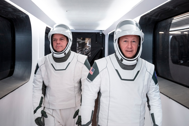 NASA astronauts Bob Behnken, left, and Doug Hurley, wearing SpaceX spacesuits, walk through the Crew Access Arm connecting the launch tower to the SpaceX Crew Dragon spacecraft during a dress rehearsal at NASA's Kennedy Space Center in Florida on Jan. 17, 2020. A SpaceX Falcon 9 rocket and Crew Dragon spacecraft stand on the launch pad at Launch Complex 39A ahead of the company's uncrewed In-Flight Abort Test. The flight test will demonstrate the spacecraft's escape capabilities in preparation for crewed flights to the International Space Station as part of the agency's Commercial Crew Program. Behnken and Hurley are slated to fly on the company's first crewed mission, Demo-2.