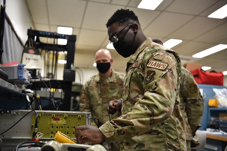 U.S. Air Force Airman 1st Class Simisola Mark, 35th Operations Support Squadron radar airfield weather system technician, uses a multimeter to test the voltage on an AN/GRC-171 transceiver for Col. Timothy Murphy, 35th Fighter Wing vice commander, and Chief Master Sgt. Joey Meininger, 35th Fighter Wing command chief, during a Wild Weasel Walk-Through at Misawa Air Base, Japan, May 24, 2021.