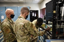 U.S. Air Force Airman 1st Class Simisola Mark, 35th Operations Support Squadron radar airfield weather system technician, adjusts an oscilloscope for Col. Timothy Murphy, 35th Fighter Wing vice commander, and Chief Master Sgt. Joey Meininger, 35th Fighter Wing command chief, in a Wild Weasel Walk-Through at Misawa Air Base, Japan, May 24, 2021.