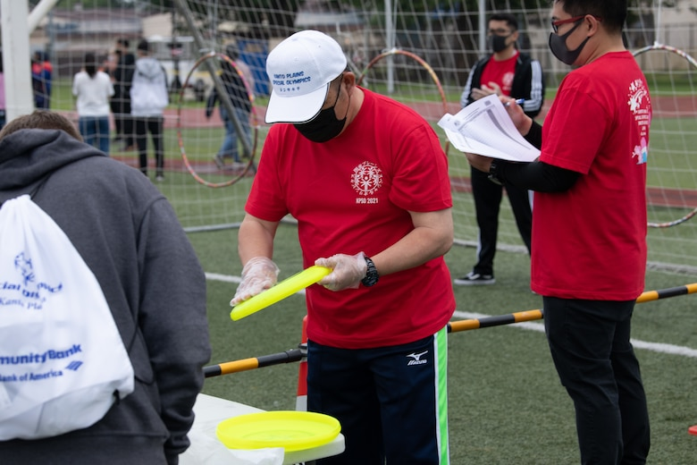 A volunteer cleans a flying disk during the Kanto Plains Special Olympics