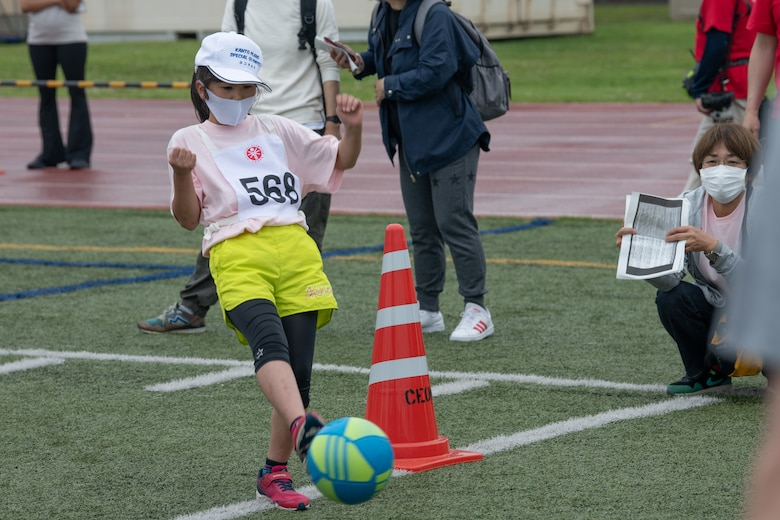 An athlete kicks a soccer ball during the Kanto Plains Special Olympics
