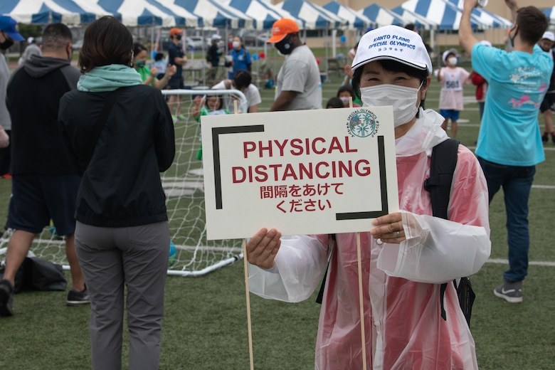 A volunteer displays a physical distancing sign during the Kanto Plains Special Olympics