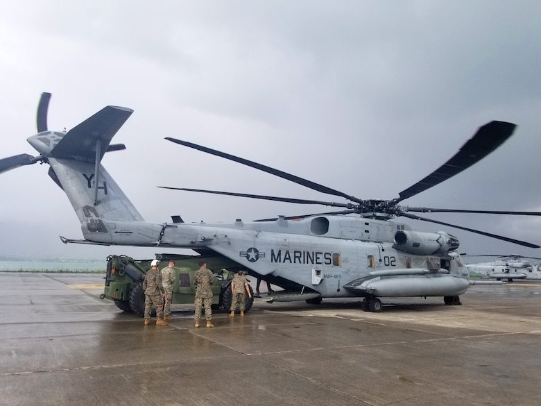 U.S. Marines load lumber and cement into the back of a CH-53 in preparation to send it to Camp Paumalu Girl Scout camp where a joint-service effort is being made to renovate and improve the camp here May 18.
