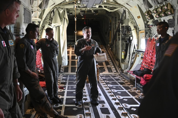 Coast Guard Lt. Cmdr. James Willette briefs the crew and passengers of the HC-130 Hercules airplane prior to departure, May 18, 2021, in Elizabeth City, NC. The crew from Air Station Elizabeth City participated in a joint-service search and rescue exercise with the Navy, the Marines and the Air Force in order to test communication capabilities in the event of a joint-service response. (Coast Guard photo by Petty Officer Third Class Emily Velez/Released)
