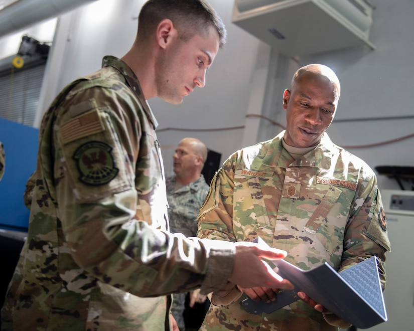 Chief Master Sgt. of the Air Force Kaleth O. Wright, right, checks out a piece of 3D printed material with Staff Sgt. March Tiche, 60th Maintenance Squadron aircraft metals apprentice, during his tour Sept. 23, 2019, at Travis Air Force Base, California. Wright arrived at Travis AFB for a three-day visit to meet with Airmen and get a firsthand look at how Team Travis contributes to rapid global mobility. (U.S. Air Force photo by Louis Briscese)