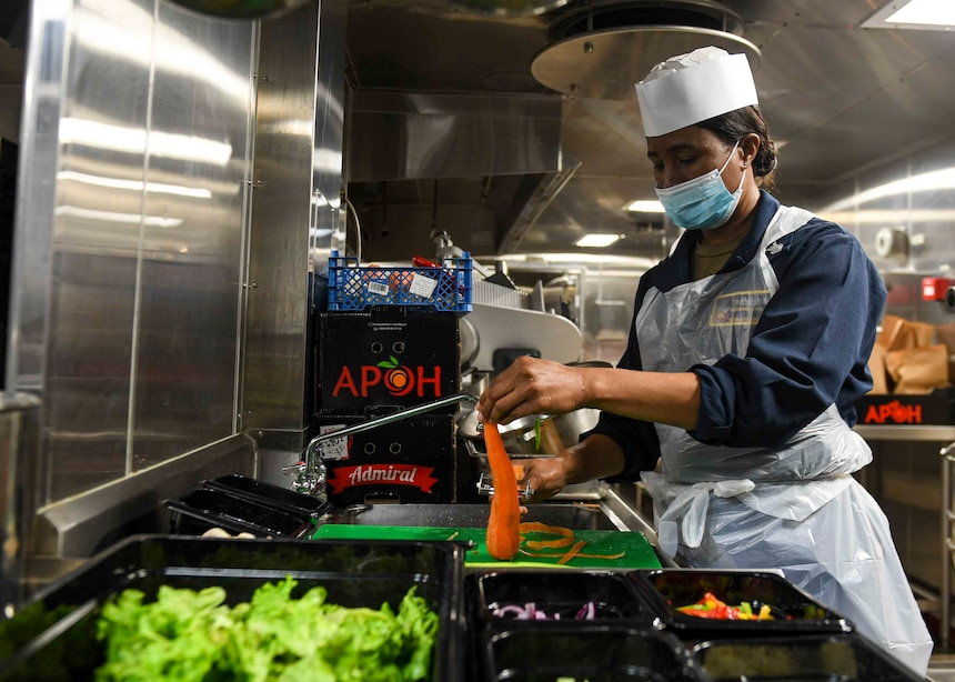 Culinary Specialist 1st Class Kaydine Erskine prepares vegetables for the lunch time salad bar.