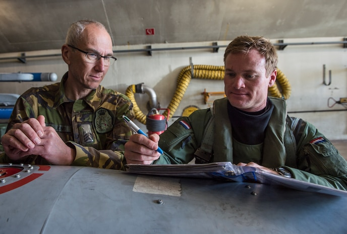 Sgt. Rinke deJong, a Dutch crew chief with the 322nd Squadron, looks over flight records with U.S. Air Force Exchange Pilot Maj. Kevin Sweeney at Leeuwarden Air Base, Netherlands, March 27, 2017 during the NATO air forces' Frisian Flag training exercise. Nearly 300 Airmen and 12 F15C are participating in Frisian Flag at Leeuwarden Air Base. The122nd Expeditionary Fighter Squadron conducted training alongside NATO allies to strengthen interoperability and demonstrate U.S. commitment to the security and stability of Europe. During Frisian Flag NATO air forces conducted air defense missions, offensive missions, missions to protect other aircraft and missions carried out to eliminate static and dynamic targets on land or at sea. (U.S. Air Force Photo/Master Sgt. Brian Ferguson)