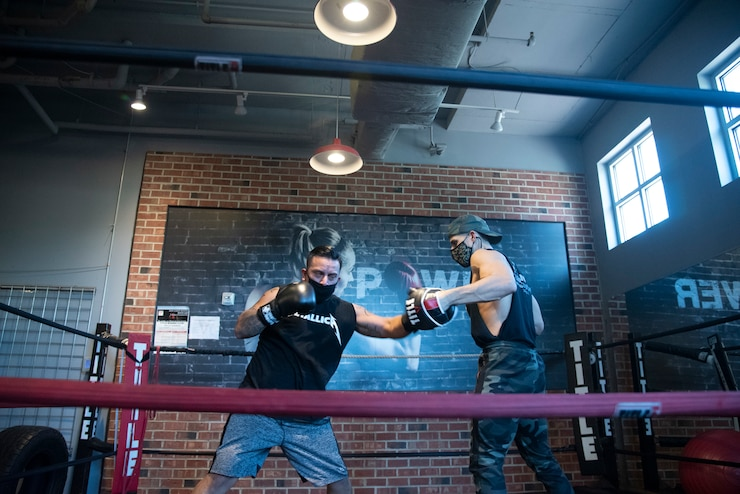 Service member spars in boxing ring.