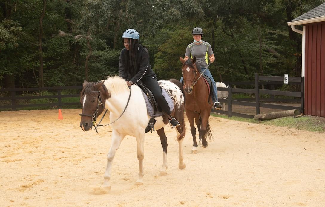 Service members ride horses in fenced-in pen.