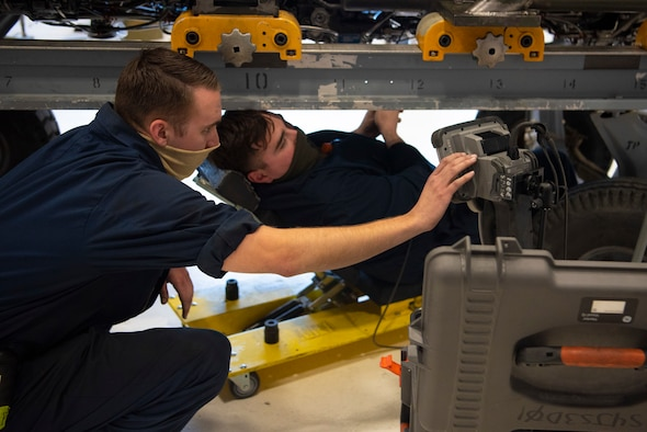 Senior Airman Steven Martin, left, and Staff Sgt. James Leonard, 49th Component Maintenance Squadron jet engine intermediate maintenance craftsmen, use a borescope to inspect narrow and hard-to-reach areas inside a F-16 Viper engine, May 13, 2021, on Holloman Air Force Base, New Mexico. The 49th CMS provides on and off-equipment maintenance support for assigned F-16 aircraft enabling Combat Air Force pilot training. (U.S. Air Force photo by Airman 1st Class Jessica Sanchez)