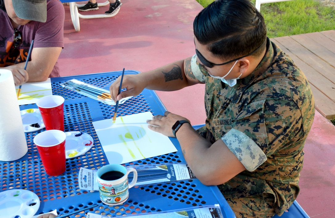 U.S. Marine paints with water colors.