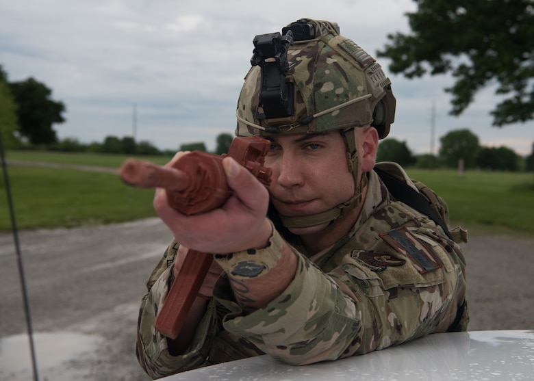 a 509th Security Forces Squadron Airman aims a training rifle while bracing against a police car.