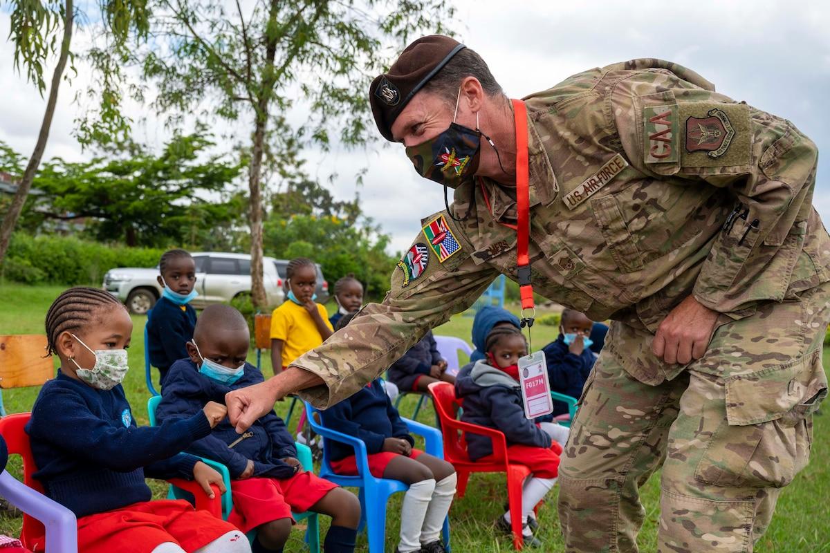 An airman fist bumps a child as other children sit beside.