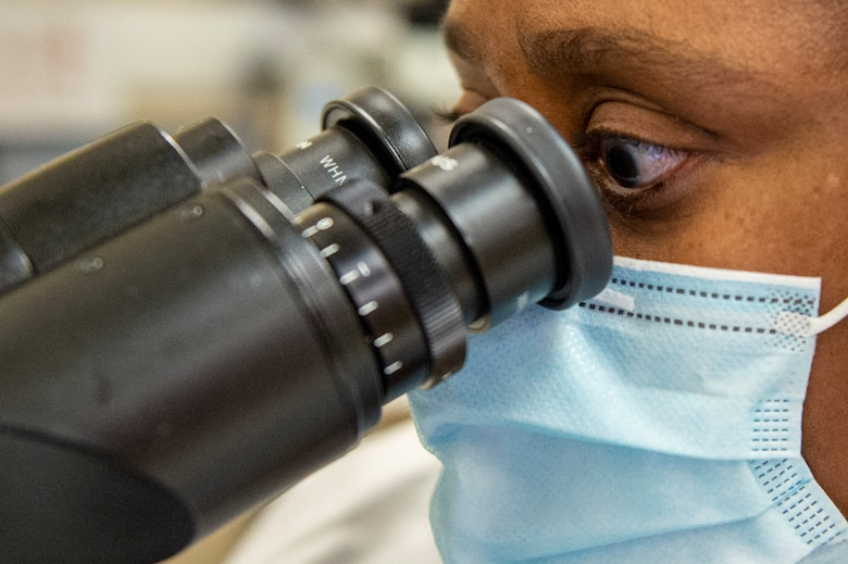 Phyllis Trigg, a medical laboratory technician with the 88th Medical Group, examines a slide under a microscope inside the Wright-Patterson Air Force Base, Ohio Medical Center, April, 28, 2021. The medical center is open 24 hours a day with medical personnel standing by to treat anyone that comes through their door. (U.S. Air Force photo by Wesley Farnsworth)