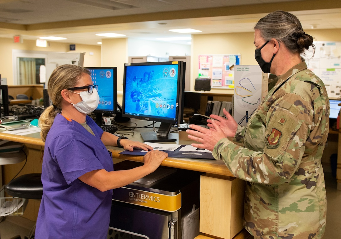 U.S. Air Force Col. Rachelle Hartze, 88th Medical Group master clinician and evening shift in-house supervisor, talks with Capt. Angela Leonardo, a registered nurse with the 88th Medical Group, inside the emergency room of the Wright-Patterson Air Force Base, Ohio Medical Center, April, 28, 2021. The medical center is open 24 hours a day with medical personnel standing by to treat anyone that comes through their door. (U.S. Air Force photo by Wesley Farnsworth)