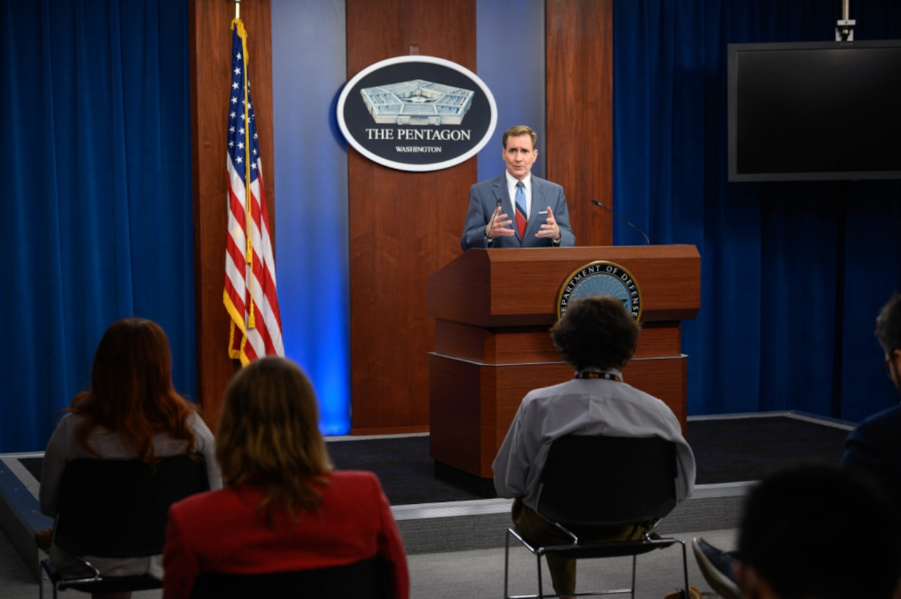 A man stands at a lectern while briefing seated  reporters.