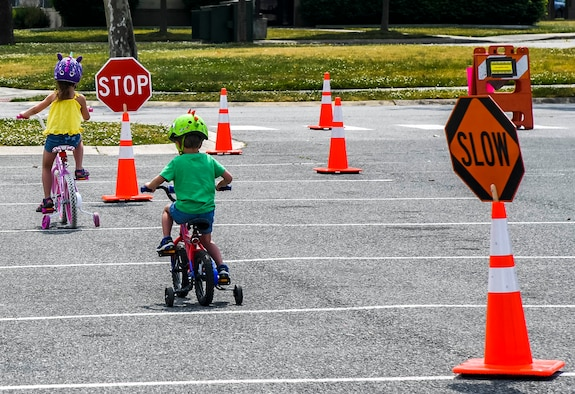 Children ride their bikes through an obstacle course during the Bicycle Rodeo at Dover Air Force Base, Delaware, May 22, 2021. Children tested their stopping and starting skills while maneuvering through a serpentine path, as well as a simulated crosswalk and pedestrian obstacles. (U.S. Air Force photo by Airman 1st Class Stephani Barge)