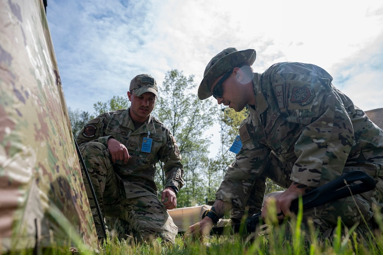 U.S. Air Force Staff Sgt. Steven Smallcombe, left, and Staff Sgt. Daniel Thevenet, right, 321st Contingency Response Squadron close precision engagement team members, setup a tent at Alpena Combat Readiness Training Center, Michigan, May 23, 2021, during Exercise Mobility Guardian 2021. The team is custom designed to roll out the back of a mobility aircraft with everything needed to operate for a few days while gaining command and control of an airfield to begin supporting the joint force with a minimal footprint. (U.S. Air Force photo by Senior Airman Aaron Irvin)