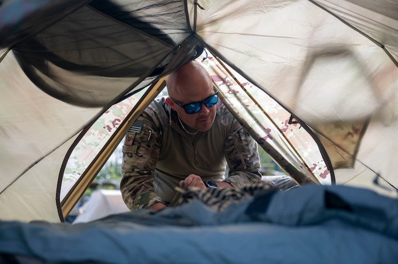 U.S. Air Force Tech. Sgt. Lance Oakes, 321st Contingency Response Squadron fireteam lead, sets up a tent at Alpena Combat Readiness Training Center, Michigan, May 23, 2021, during Exercise Mobility Guardian 2021. The team is custom designed to roll out the back of a mobility aircraft with everything needed to operate for a few days while gaining command and control of an airfield to begin supporting the joint force with a minimal footprint. (U.S. Air Force photo by Senior Airman Aaron Irvin)