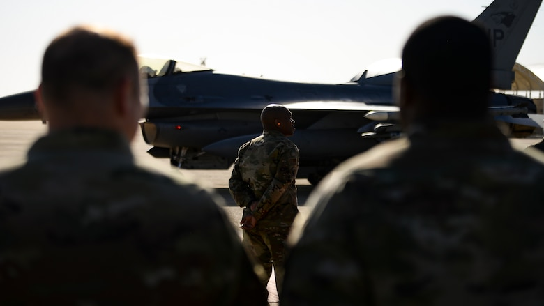 A command chief waits for his commander to exit a jet after his final flight.