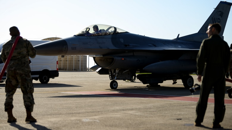 A vice commander and command chief wait for their commander to exit a jet after his final flight.