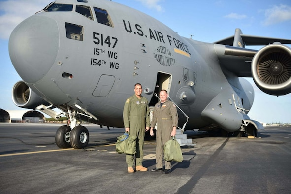 U.S. Navy Capt. Erik Spitzer, Joint Base Pearl Harbor-Hickam commander, and U.S. Air Force Col. Dan Dobbels,15th Wing commander, flew a C-17 together to demonstrate the U.S. Navy and U.S. Air Force partnership in securing stability in the Indo-Pacific region at Joint Base Pearl Harbor-Hickam, Hawaii, May 4, 2021. On Oct. 1, 2010, Naval Station Pearl Harbor joined with Hickam Air Force Base to become Joint Base Pearl Harbor-Hickam, Hawaii, to support both Air Force and Navy missions in the Pacific.  (U.S. Air Force photo by Tech. Sgt. Anthony Nelson Jr. )