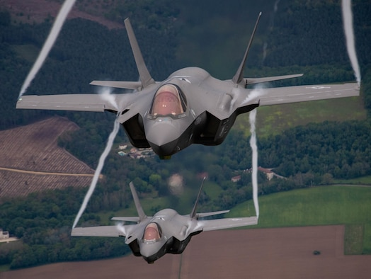 Two fighter aircraft flying towards the camera, one on top of the other.