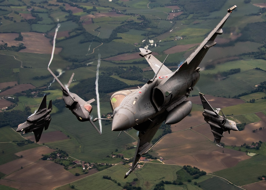 four fighter aircraft flying towards the camera, tilted as if all about to fly around the photographer.