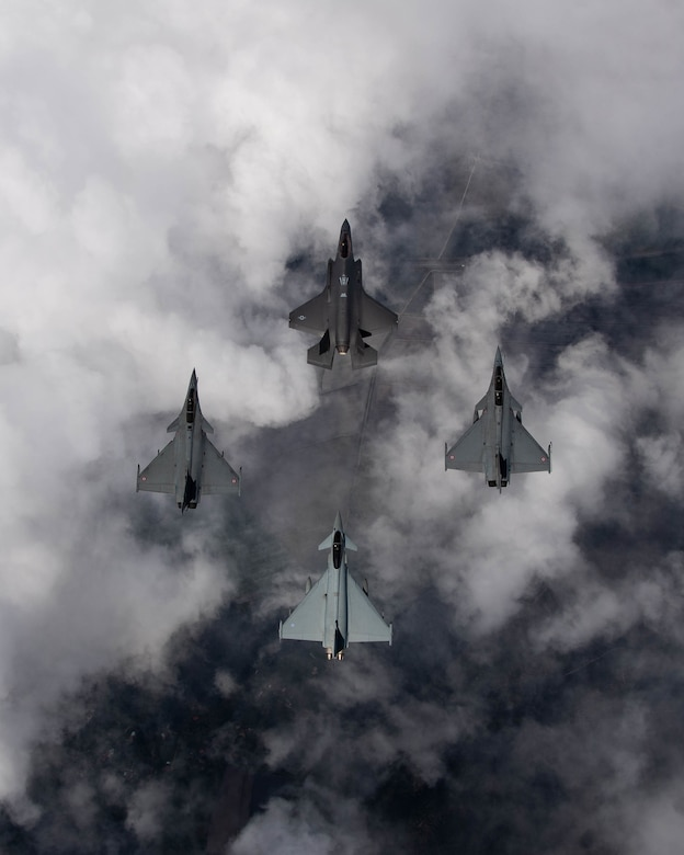 Four fighter aircraft flying in a diamond formation, looking at them from above