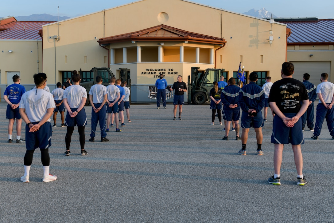 U.S. Air Force Senior Master Sgt. Timothy Okkerse, 724th Aircraft Maintenance Squadron superintendent, center, gives opening remarks before a 'Port Dawg' memorial run at Aviano Air Base, Italy, May 27, 2021. The 'Port Dawg' memorial run is an annual event which honors 12 fallen teammates from the career field with a 2.5 mile run. Port Dawgs are transportation specialists serving at aerial ports around the world. (U.S. Air Force photo by Airman 1st Class Brooke Moeder)