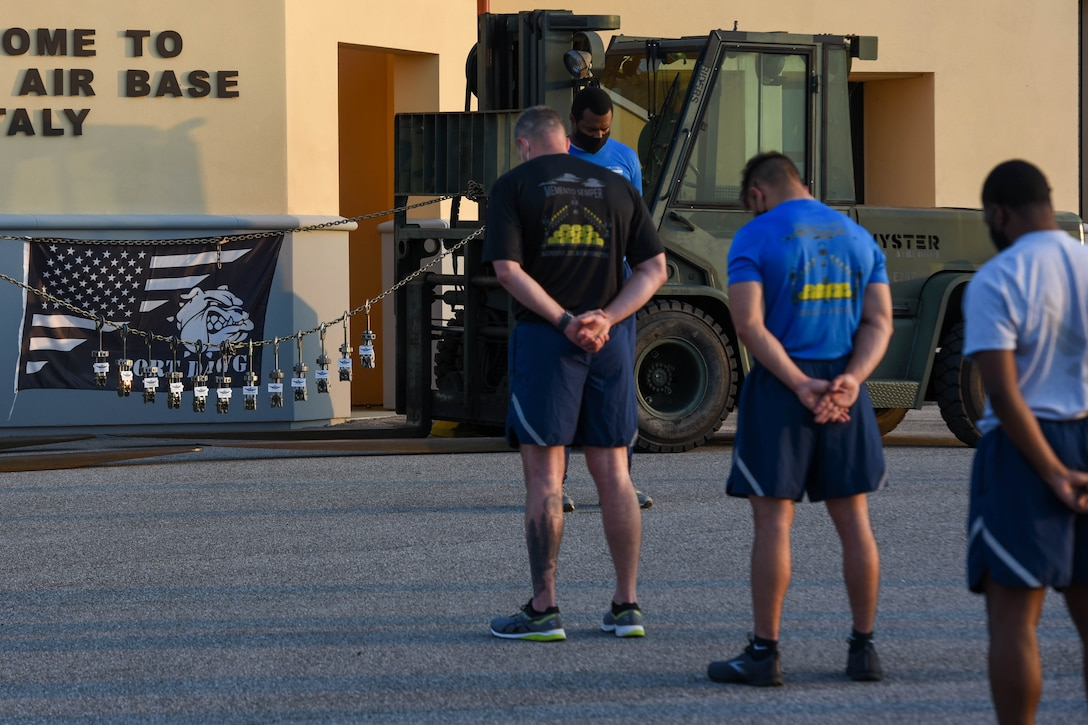 Members of the 724th Aircraft Maintenance Squadron observe a moment of silence before a 'Port Dawg' memorial run at Aviano Air Base, Italy, May 27, 2021. The run is held annually throughout the career field as a way to honor members who have fallen while serving as a 'Port Dawg.' The event is an opportunity to highlight the importance of the Port Dawgs in the AMS installations and community. (U.S. Air Force photo by Airman 1st Class Brooke Moeder)