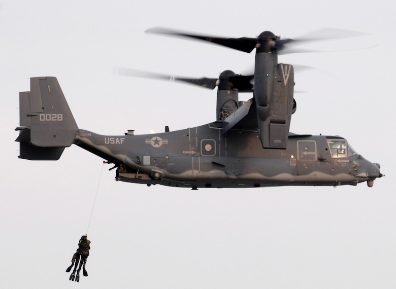 Two Navy Seals get hoisted up into a CV-22 Osprey during a training mission June 28.  The Osprey and aircrew are from the 8th Special Operations Squadron at Hurlburt Field, Fla.  ( U.S. Air Force photo/Senior Airman Andy M. Kin)