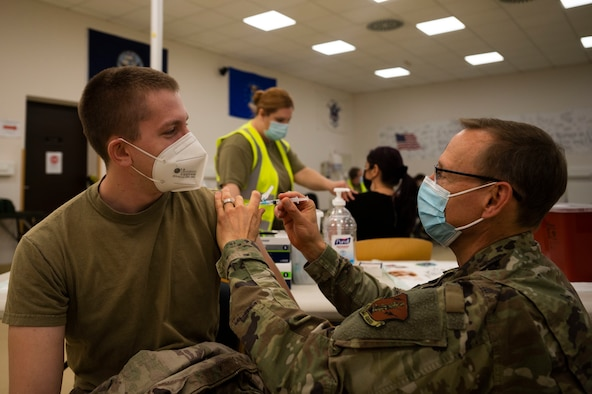 U.S. Air Force Senior Airman Bradley Frank, 435th Construction and Training Squadron command aircraft arresting systems DEPO technician, receives a COVID-19 vaccine from Senior Master Sgt. Michael Seymour, registered nurse and active Guardsman with the 603rd Air Operations Center combat operations, at Ramstein Air Base