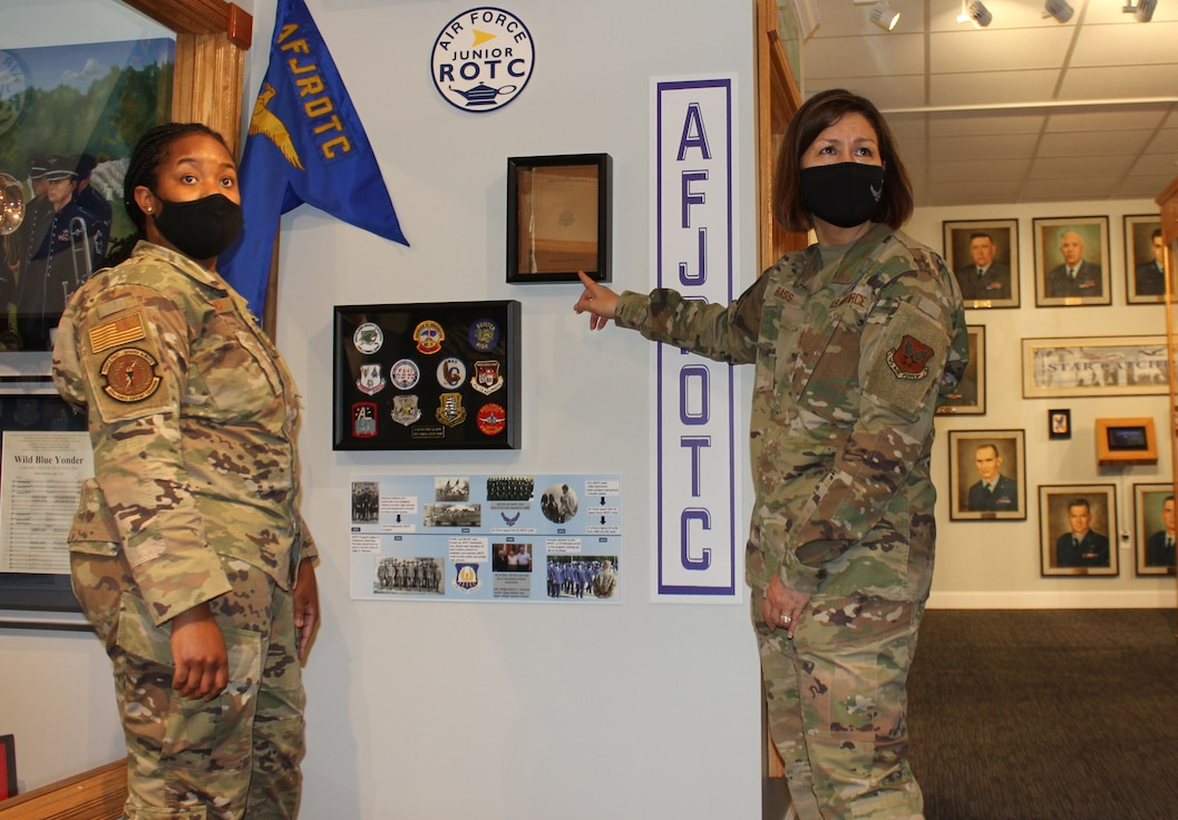 Staff Sgt. Tikeya Strong (left), Headquarters Air Force Junior ROTC, and Chief Master Sgt. of the Air Force JoAnne Bass discuss the new JROTC enlisted instructor legacy display at the Air Force Enlisted Heritage Research Institute, May 12, 2021, at Maxwell-Gunter Annex, Alabama. Strong spearheaded the display, which honors the dedication that AFJROTC enlisted instructors have by continuing to serve the nation past their 20 years on active duty. (U.S. Air Force photo by Christian Hodge)