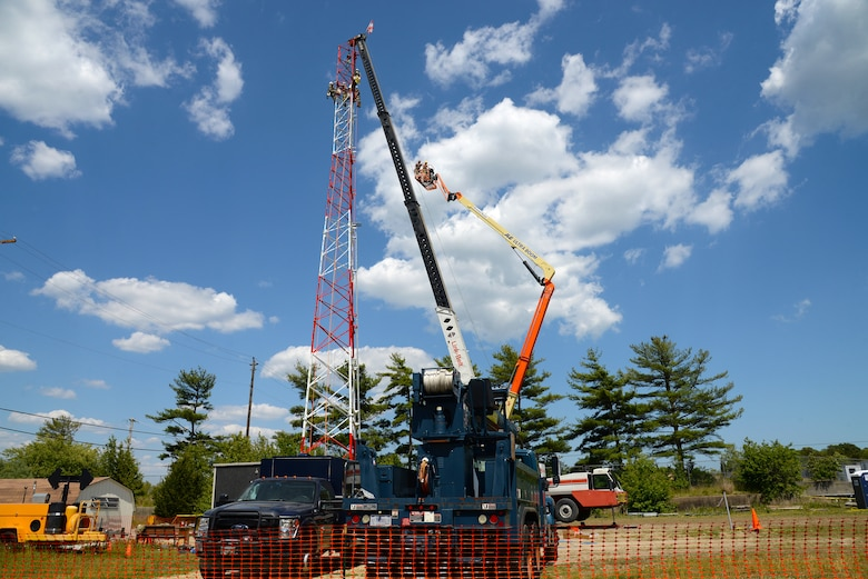An image of Airmen with the Massachusetts and Pennsylvania Air National Guard working in unison, using climbing gear to secure themselves safely to a tower, operating a high lift for inspection purposes and using a mobile crane to hoist and connect the top section of a radio communications tower.