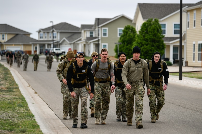 A group of Airmen marches through a suburban style neighborhood with heavy backpacks.