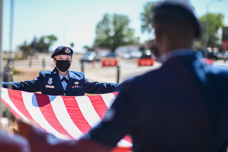 Two Security Forces Airmen in their dress blues uniform hold a flag open as they stand at the position of attention.