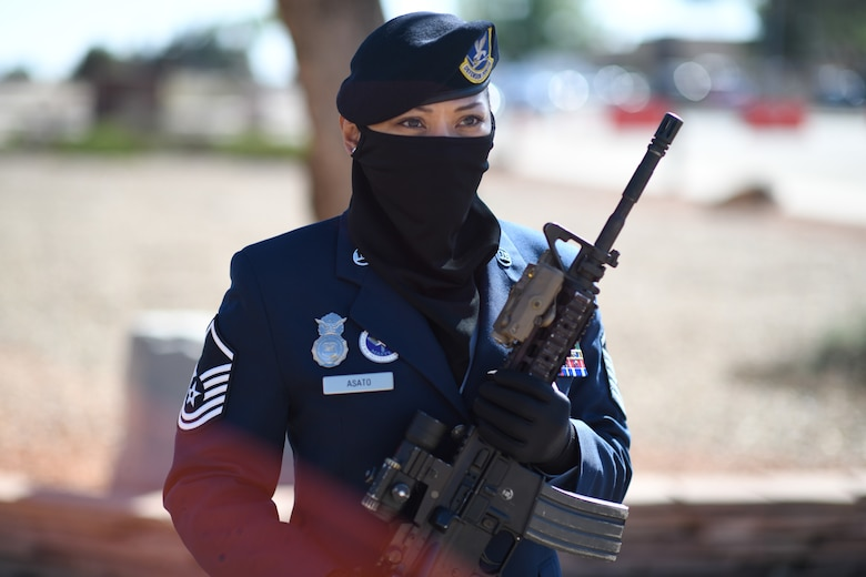A Security Forces Master Sergeant in her dress blues uniform stands at attention and holds an M4 rifle in the 'port-arms' position.