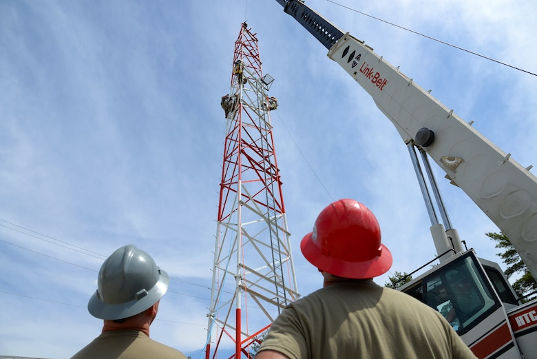 An image of Airmen with the Massachusetts and Pennsylvania Air National Guard using climbing gear and operating a mobile crane to hoist and connect a section of radio communications tower.