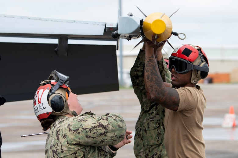 U.S. Navy Aviation Ordnancemen secure missile to an aircraft