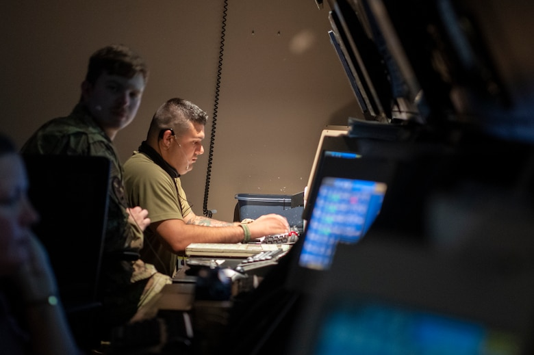 U.S. Air Force Airman sits in front of computer screen