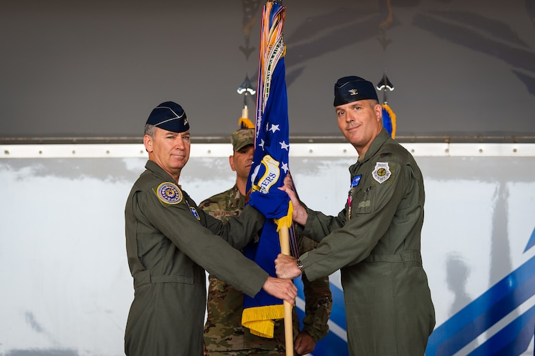 A photo of the 15th Air Force commander receiving a guidon from the former commander of the 23d Wing