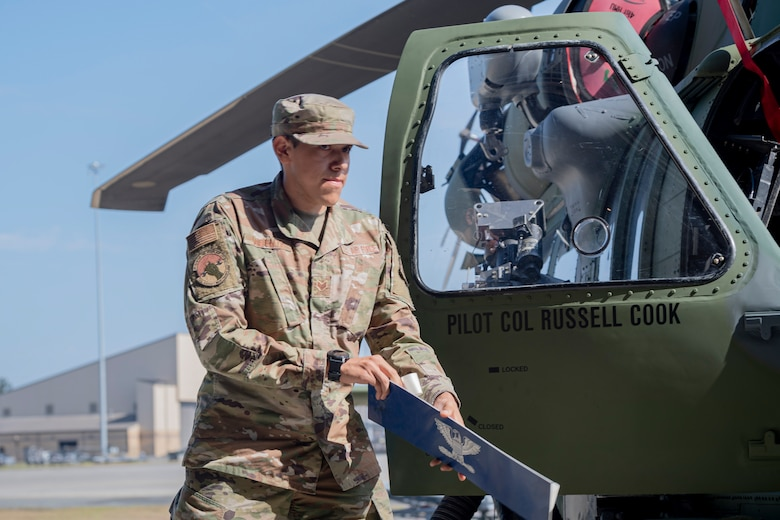 A photo of an Airman revealing a name on a helicopter