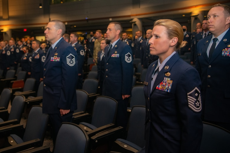Graduates of Class 21-E stand for the arrival of the official party at a graduation ceremony at the Senior Noncommissioned Officer Academy on Maxwell-Gunter Annex, Alabama, May 26, 2020. The SNCOA held its first in-person graduation ceremony since the World Health Organization declared COVID-19 a pandemic in March 2020.
