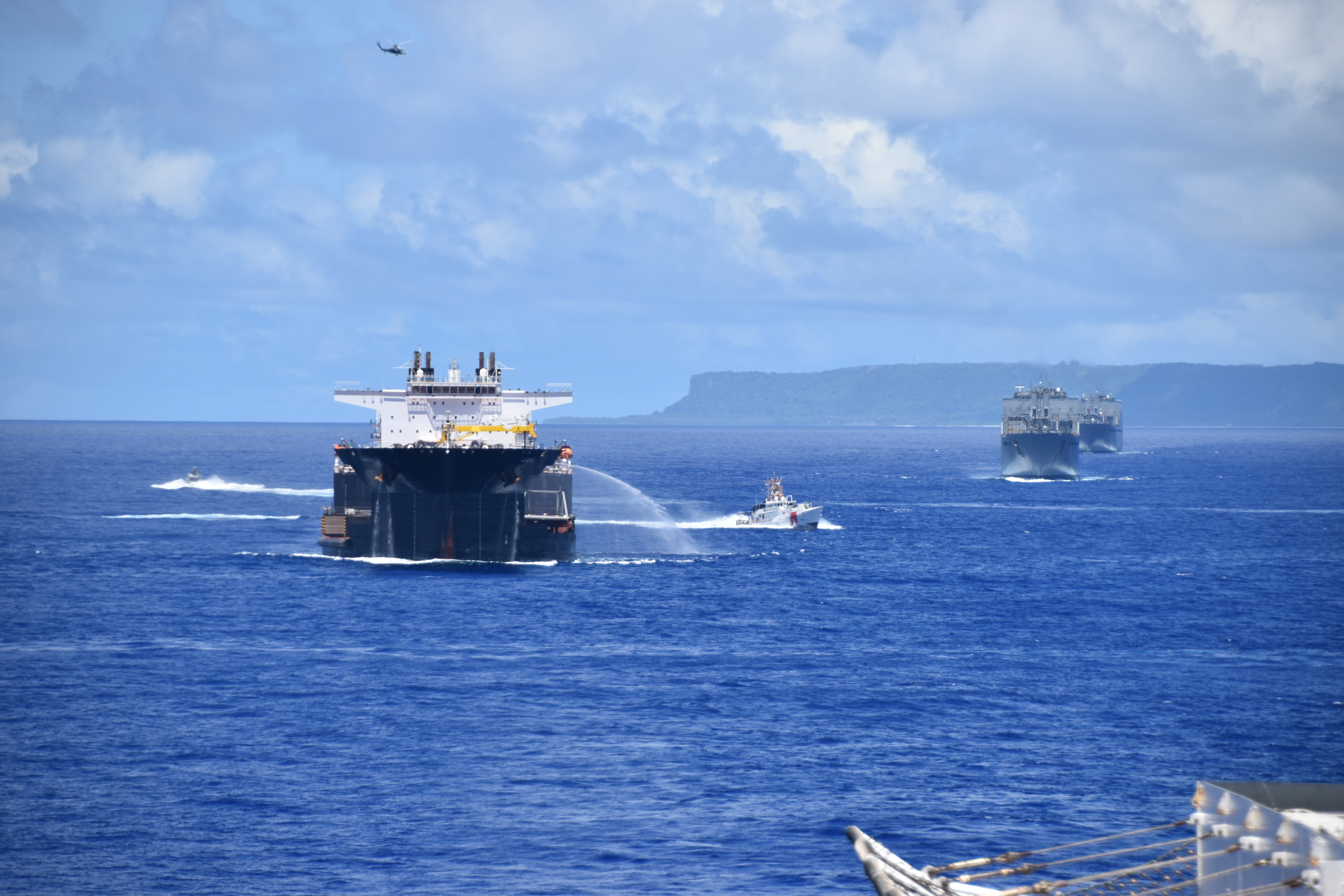 While steaming in a formation near Guam, USNS Montford Point employs their hose, a pre-planned response, which it might use during convoy operations.  Pictured from left are:  a Coastal Riverine Group 1's mark VI boat, USNS Montford Point (T-ESD 1), U.S. Coast Guard Cutter Myrtle Hazard (WPC-1139), USNS Red Cloud (T-AKR 313), USNS Watkins (T-AKR 315), and in the air, an MH-60R from Helicopter Sea Combat Squadron 25.
